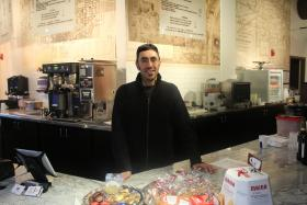 Man stands behind counter at coffee shop