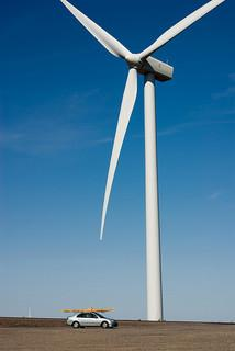 Photo of a Wind Turbine in Washington, small car with Kayak in the foreground.