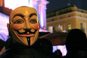 A protester in Madrid, Spain, wears a Guy Fawkes mask associated with the hacker group Anonymous