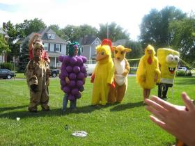 Interns wearing ridiculous costumes, such as a camel, a cluster of grapes, a chicken, a kangaroo, and Sponge Bob, stand in a line, prepared to participate in some kind of sport involving tennis rackets.
