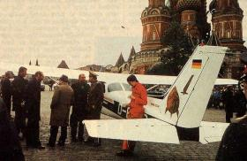 Mathias Rust leans against his Cessna in Red Square, while Soviet officials stand around in a group nearby