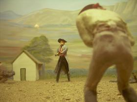 In this detail of a diorama showing the gunfight at the O.K. Corral, a man doubles over in pain, apparently shot by a distant gunman.