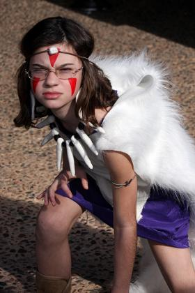 Complete with facepaint, a furry cape and a necklace seemingly made of dinosaur teeth, a young girl with glasses strikes a fierce Princess Mononoke pose.