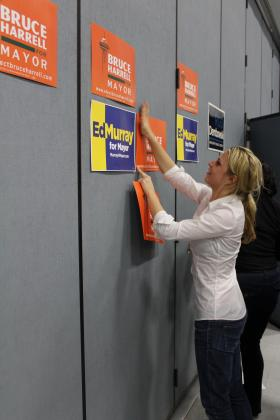 A campaign worker puts up signs at the 46th District Democrats endorsement meeting