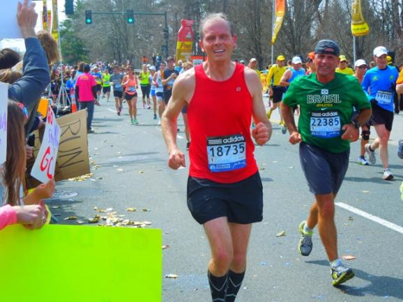 62-year-old Jeff Poppe (in red) at the 26-mile mark.