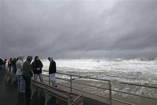 People watch wave activity at Rockaway beach Monday, Oct. 29, 2012, in New York. Sandy, a Category 1 hurricane with sustained winds of 75 mph and the center of the storm is expected to be near the mid-Atlantic coast on Monday night.