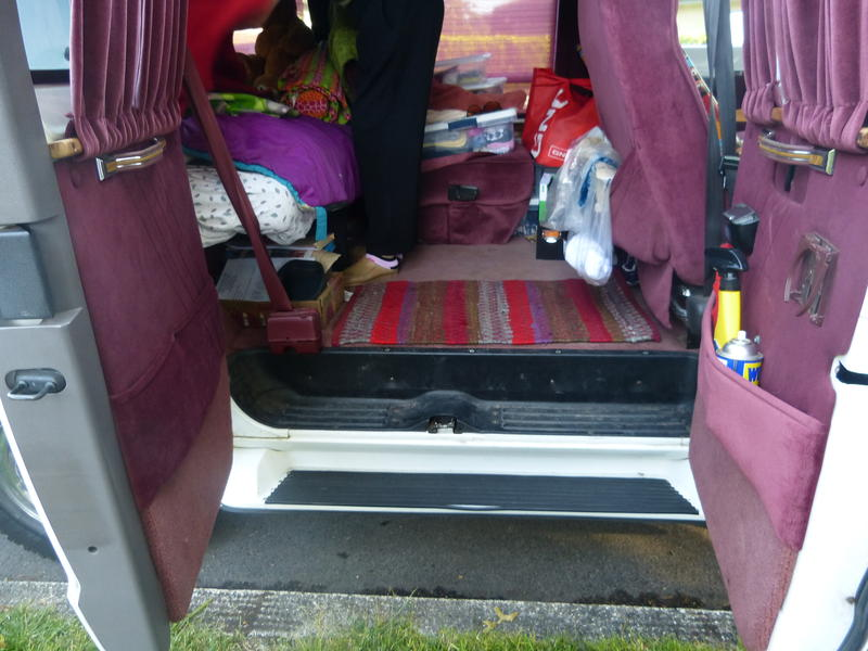 The back of Elizabeth Jay's Dodge Ram minivan is cluttered with her clothes and supplies because the van is her living room and bedroom.