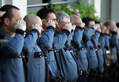 Seattle Police Officers salute during a memorial service, 2006.