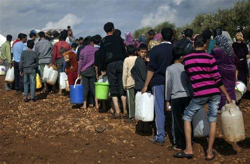 Syrians who fled from the violence in their village, carry plastic containers as they line up to fill them with water at a displaced camp in the Syrian village of Atma, near the Turkish border with Syria. Nov. 10, 2012.