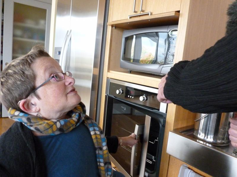 Karen Braitmayer demonstrates the accessibility of appliances in her kitchen.