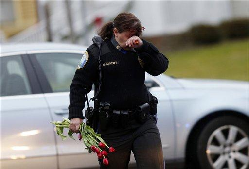Newtown Police Officer Maryhelen McCarthy carries flowers near a memorial for shooting victims Sunday, Dec. 16, 2012 in Newtown, Conn.