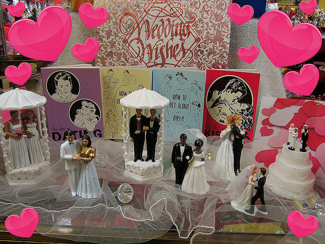A display of wedding cake figurines featuring same sex couples.