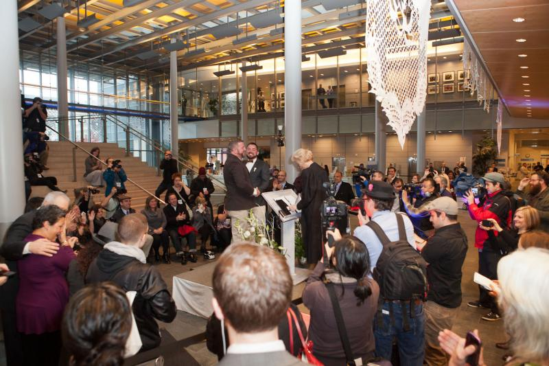 Family, friends and media gather in the Grand Lobby of Seattle's City Hall to witness over 100 couples take their wedding vows.