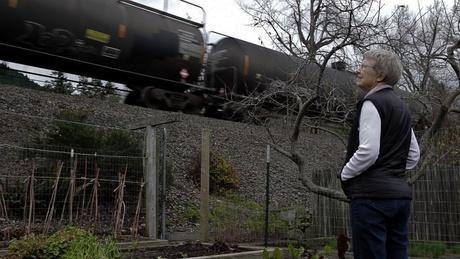 Ann Jones watches a train pass in front of her home outside of Bellingham. Trains carrying oil through the Northwest are on the rise.