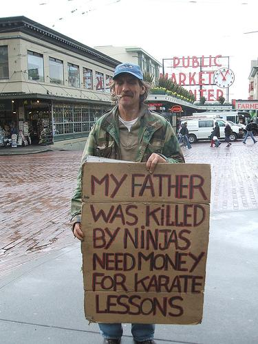 "Panhandler holds sign in front of Pike Place Market. Sign reads ""My father was killed by ninjas. Need money for karate lessons."""