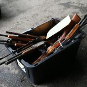 A plastic bin of assorted guns turned in by people in exchange for gift cards at Seattle's first gun buyback event in 20 years.
