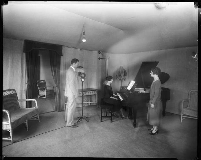 Broadcasters around a microphone in the living room-like studio of radio station KFOA in Seattle's Rhodes Department store in 1923.