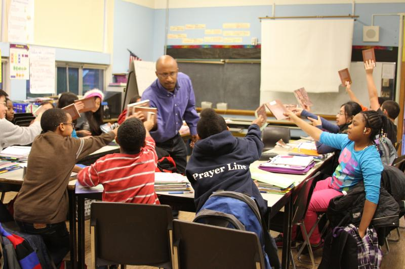 """If you're packin' heat, hold 'em high!"" Rainier Scholars teacher Drego Little greets his students' books with his own."