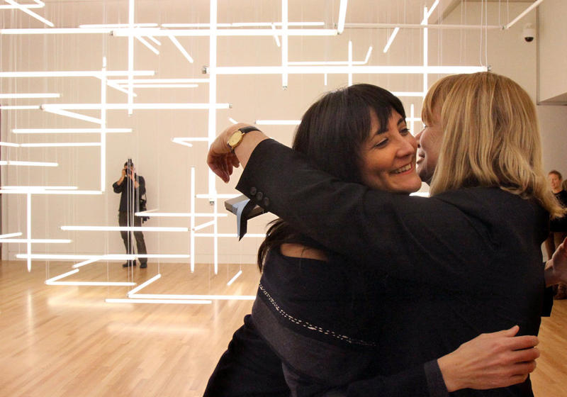 Freelance visual-arts curator Yoko Ott (left) hugs Jo-Anne Birnie Danzker, director of the Frye Art Museum, after giving her a present on Danzker's birthday.