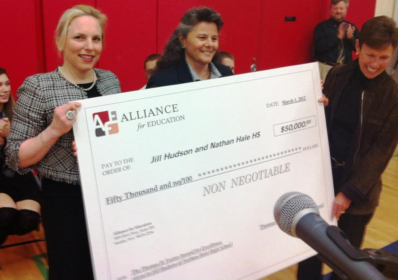 Alliance for Education President and CEO Sara Morris presents a symbolic check to Nathan Hale High School Principal Jill Hudson with Alliance board member Judy Runstad on March 1, 2012.