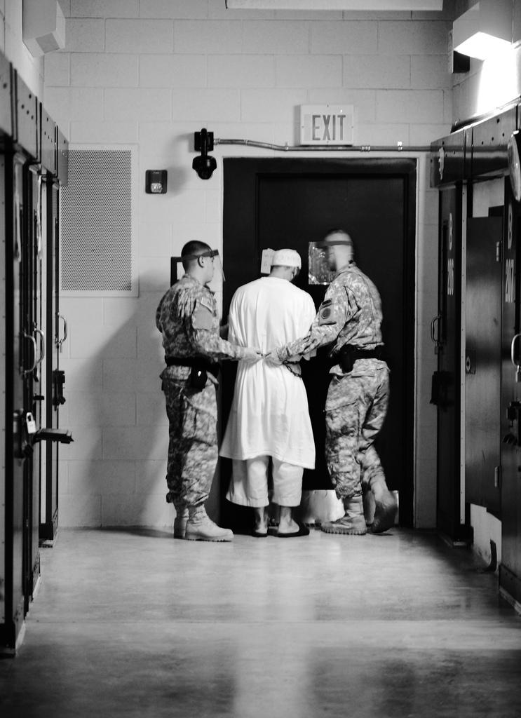 Guards from Camp 5 at Joint Task Force Guantanamo escort a detainee from his cell to a recreational facility within the camp, Oct. 2011.