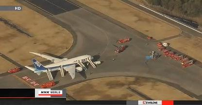 Fire trucks surround a Boeing 787 with emergency slides deployed on a runway in Japan.