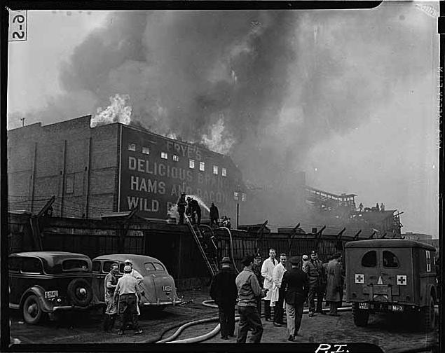 Firefighters and other emergency personnel respond to the crash of a B-29 prototype at the Frye Meat Packing Plant on February 18, 1943.  A total of 32 died on the plane and in the fire.