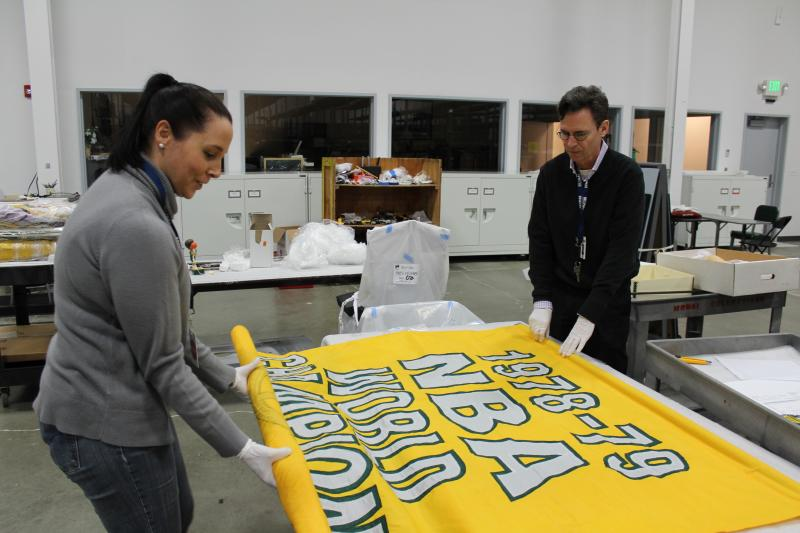 MOHAI Registrar Kristin Halunen and Executive Director Leonard Garfield with a Sonics' 1978-79 championship banner