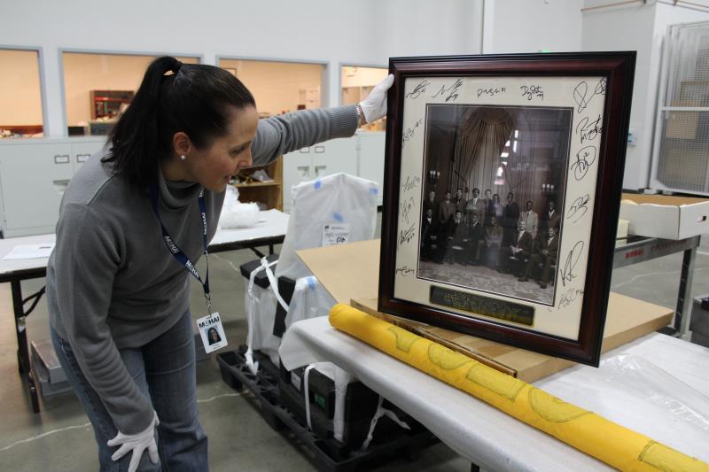 MOHAI's Kristin Halunen with a framed, signed photo of the 2005-06 Sonics team