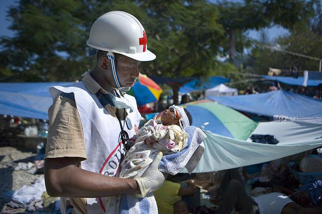 Haitian Red Cross volunteer Jean Zacharie delivers first aid to 1-month-old Deborah Fatima, January 2010.