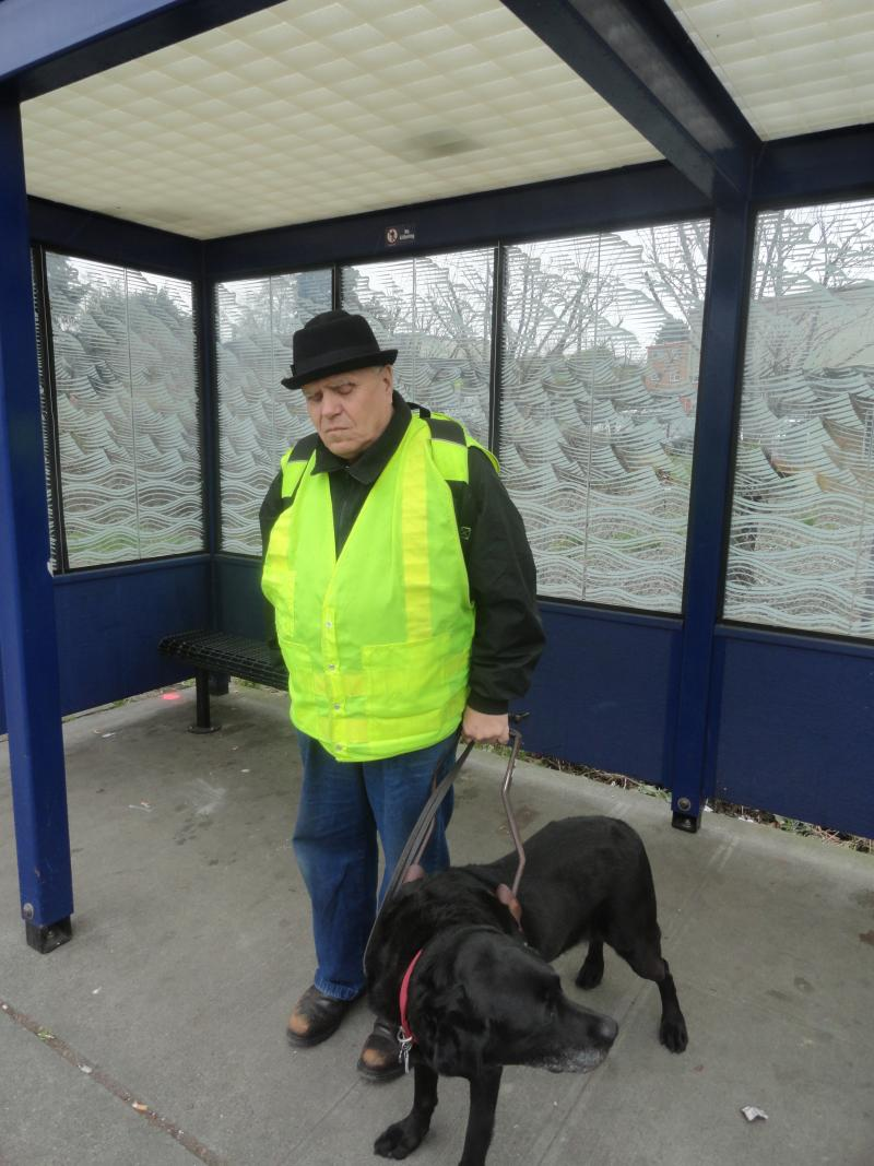 Buddy Yates and his guide dog Palmer wait for the bus.