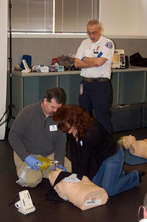 Tim Benningfield and Lanise Taunton Rigby work to revive a CPR training  mannequin under the watchful eyes of Seattle EMTs.
