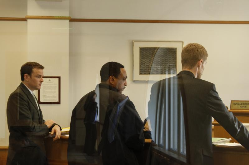 David A. Johnson stands between defense attorneys at a pretrial hearing where co-defendant Silas Potter failed to appear.