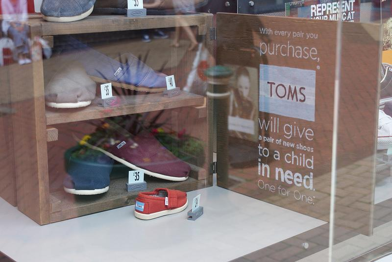 Window display of TOMS shoes, along with campaign message: One for One.