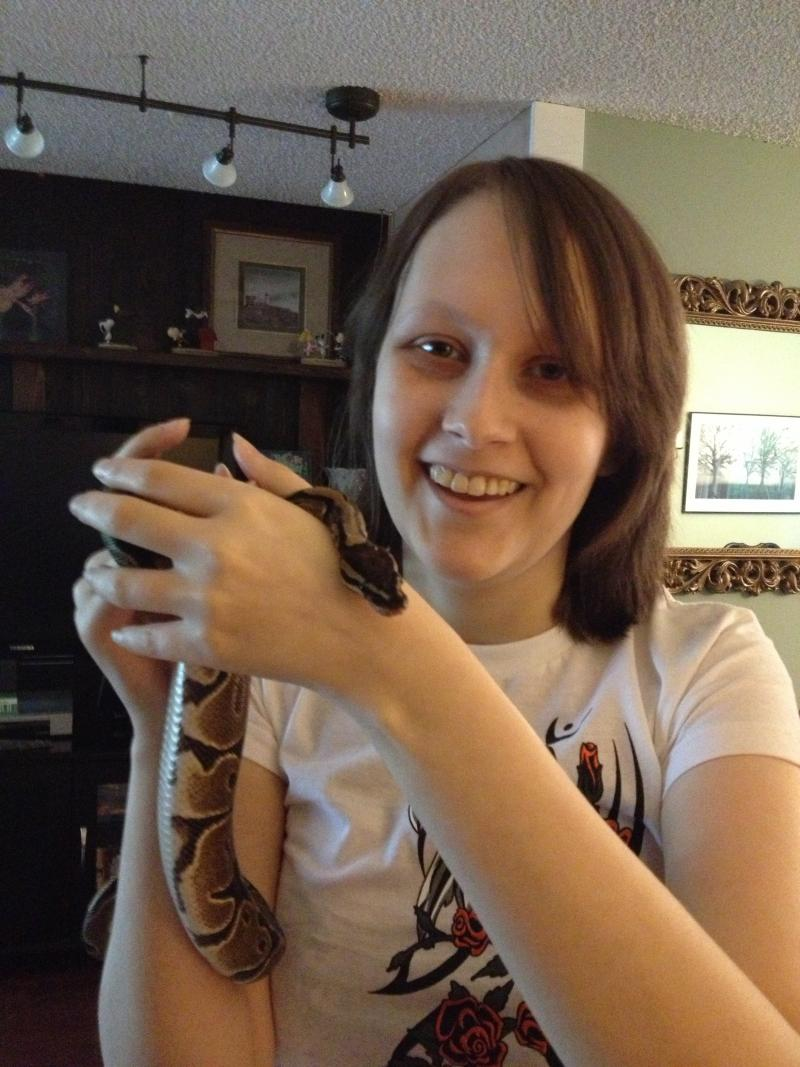 Anna Stephens with her pet snake Evra. Anna's life has been on hold for the past four years since her tumor came back. She hopes to return to school again to study reptiles and amphibians.