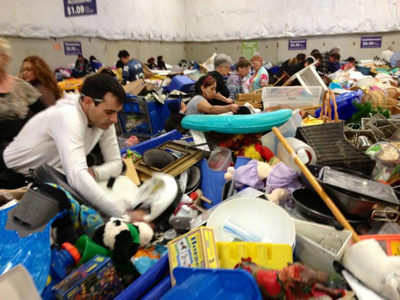 Customers dig through the bins at the Seattle Goodwill outlet. Items are purchased by weight.