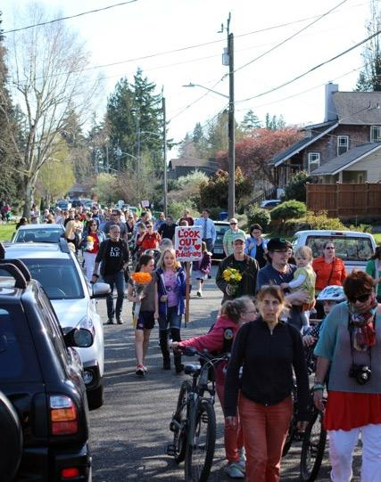 Neighbors gather for a memorial walk on April 1 along 33rd Avenue NE, heading toward the memorial site.