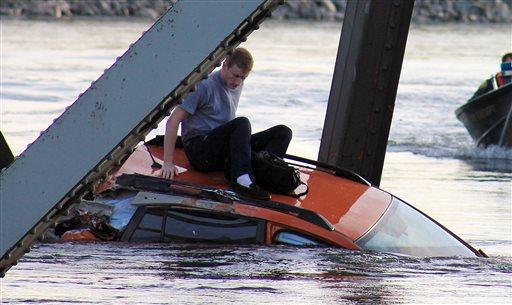 In this photo provided by Francisco Rodriguez, a man is seen sitting atop a car that fell into the Skagit River after the collapse of the Interstate 5 bridge there minutes earlier Thursday, May 23, in Mount Vernon, Wash.