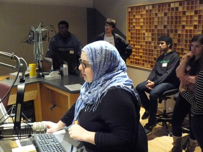 RadioActive alumna Amina Al-Sadi directs KUOW's Weekday while participants of RadioActive's Spring 2013 Workshop look on.