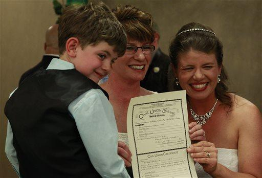 Fran Simon, left, and her partner Anna Simon, flanked by their son Jeremy, display their Colorado civil union license. They were the first couple to receive their license as the Colorado Civil Union went into effect  on May 1.