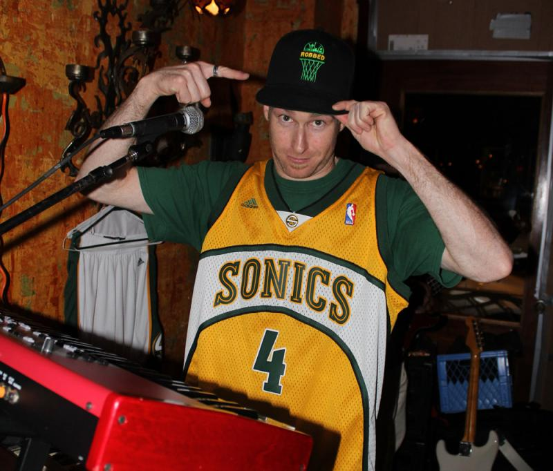 "Kiley Sullivan with the band Kore Ionz performing in Sonics gear. His hat shows the word ""robbed"" on top of a basketball net."