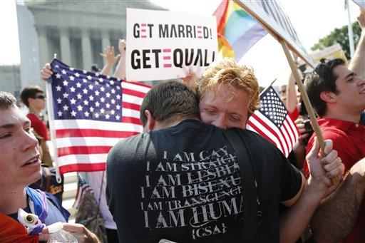 Michael Knaapen, left, and his husband John Becker, right, embrace after the Supreme Court struck down a federal provision denying benefits to legally married gay couples in front of the Supreme Court, June 26, 2013.