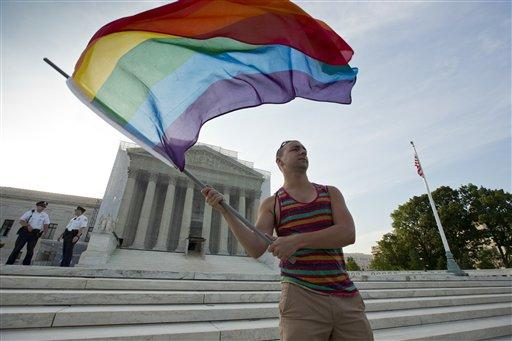 Gay rights advocate Vin Testa waves a rainbow flag in front of the Supreme Court at sun up in Washington, DC, June 26, 2013.