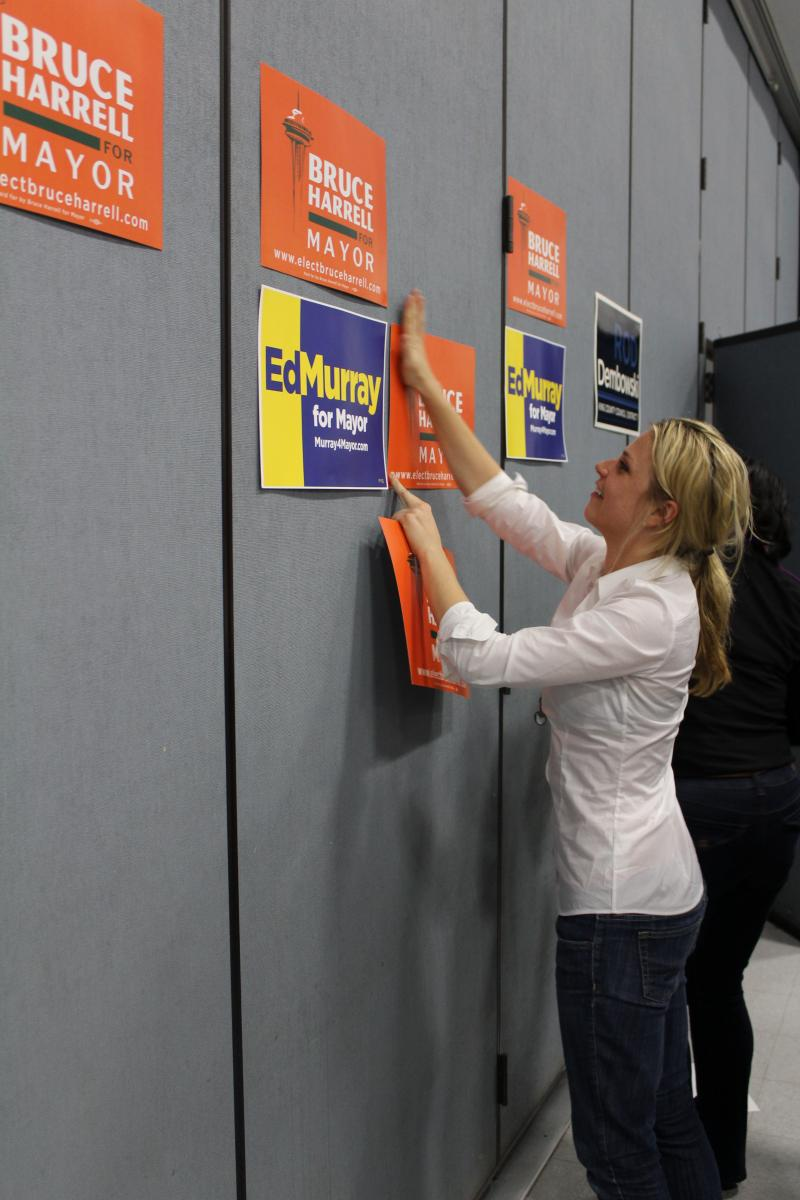 Campaign worker puts up signs at 46th District Democrats endorsement meeting