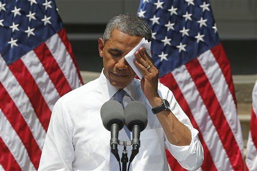 President Barack Obama wipes his face as he speaks about climate change, Tuesday, June 25, 2013, at Georgetown University in Washington.