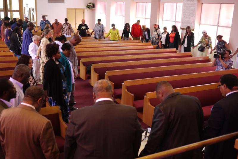 About 50 people join hands and pray during noon vigil for Trayvon Martin.