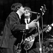 Paul McCartney and John Lennon on stage at the Coliseum.