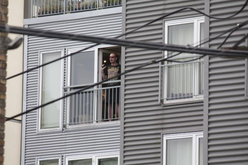 A man looking out from the fifth floor of the Marq Condos building. He was later shot by police.