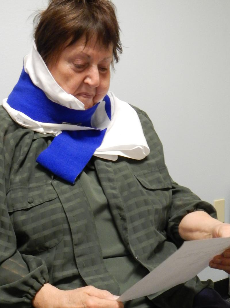 Helen Funston wears an ice wrap and reads instructions at her physical therapy appointment.