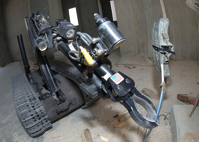 Technicians from a Explosive Ordnance Disposal unit use a robot to disarm a mine during a training mission.